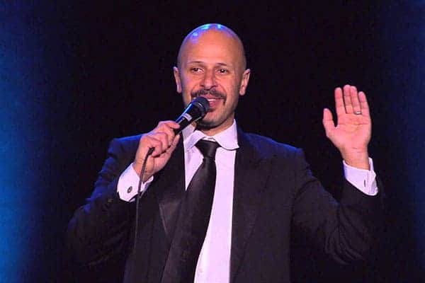 Maz Jobrani in black coat performing on stage