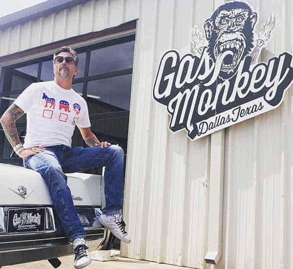 Richard Rawlings poses happily in car beside his company Gas Monkey Garage