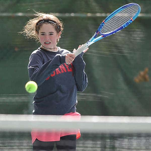 Merri Kelly playing long tennis in grey hood and pink skirt