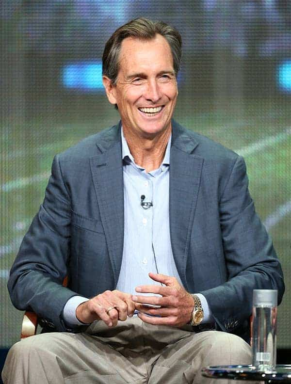 Cris Collinsworth smiling in gray coat white shirt on tv interview